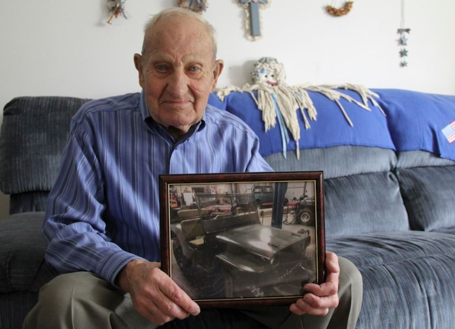 Jerry Scherer, sitting in his house in the Heights, shows a recent photograph of his restored 1945 Willys Jeep. It looks even better now. (Ed Kemmick/Last Best News)