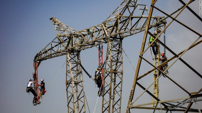 Linemen work to restore a key central transmission route. (CNN)