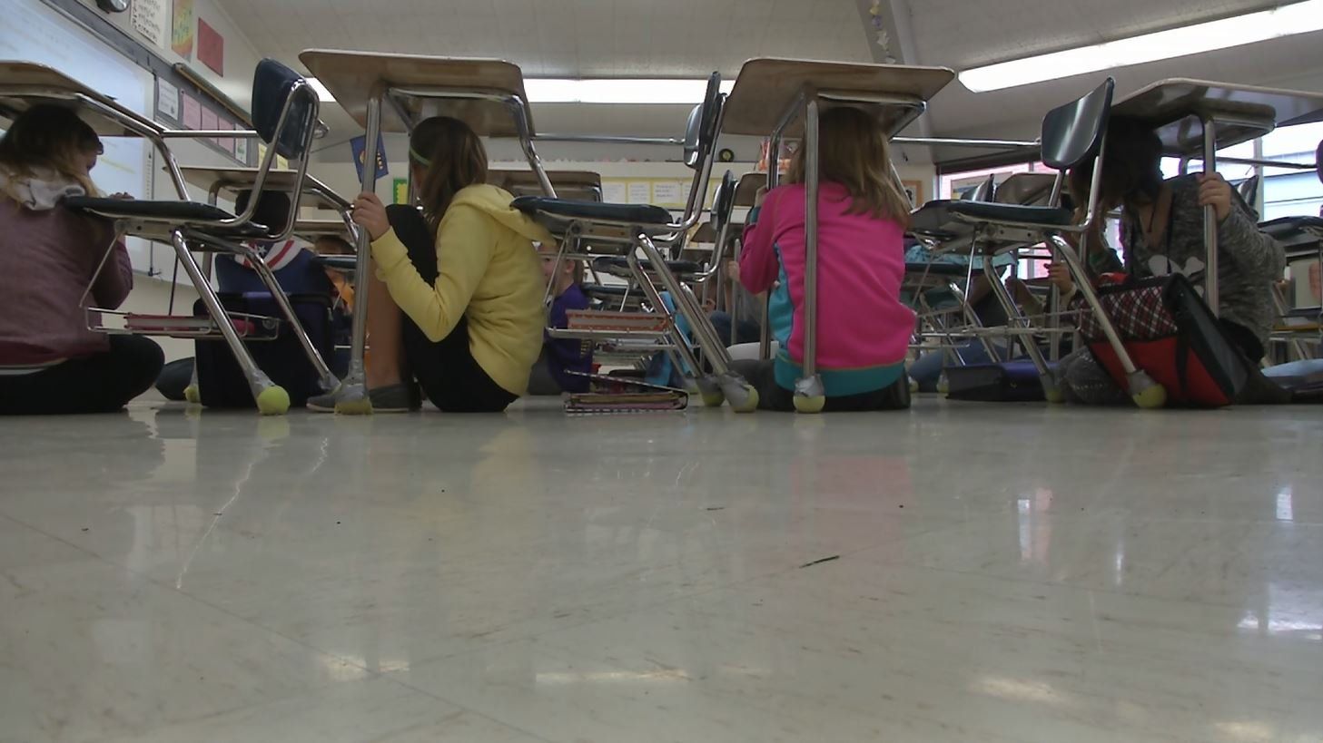 By hiding under their desks, students can protect themselves from ceiling debris in the event of an earthquake. (MTN News photo)